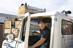 Middle Aged Male Worker Driving Truck. Portrait of a middle aged male worker driving truck Stock Photos