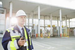 Middle-aged male worker holding walkie-talkie while looking away in shipping yard Stock Image