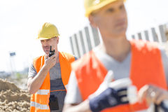 Middle-aged male worker using walkie-talkie with colleague in foreground at construction site Royalty Free Stock Photography