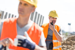 Middle-aged male worker using walkie-talkie with colleague in foreground at construction site Stock Image