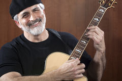 Middle-Aged Man With Acoustic Guitar. Portrait of a middle-aged man wearing a black beret and t-shirt and playing an acoustic guitar. He is smiling at the camera Royalty Free Stock Photo