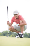 Middle-aged man aiming ball while crouching on golf course Stock Image