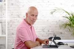 Middle-aged man alone, sitting with tablet. A middle-aged man alone, sitting with a tablet royalty free stock photography