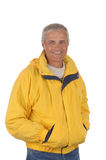 Middle aged man in anorak. Middle aged man wearing a yellow anorak isolated over white royalty free stock images