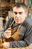 Middle-aged man in apron holding smoking pipe Royalty Free Stock Photos