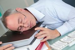 Middle aged man asleep on stack folders. Middle aged man asleep on stack of folders Stock Photo