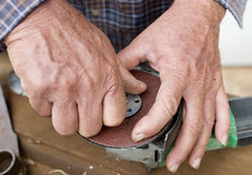 Middle-aged Man Assembling Sanding Disk on Grinder. Royalty Free Stock Photos