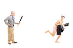 Middle aged man with baseball bat shouting at a young naked man. Full length portrait of a middle aged men with baseball bat shouting at a young naked men Royalty Free Stock Images