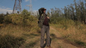 A middle aged man with a beard with a backpack walking down a mountain path. He stops, puts a hand to the forehead stock footage