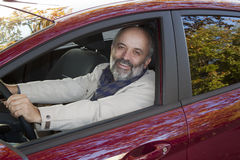 Middle-aged man driving a car. Middle-aged man with a beard driving a hot magenta car stock photo