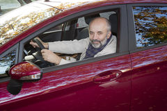 Middle-aged man driving a car. Middle-aged man with a beard driving a hot magenta car Stock Image