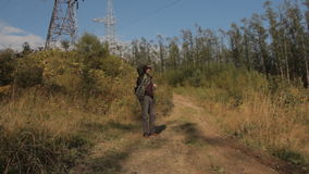 A middle aged man with a beard wearing grey pants, green jacket and yellow boots with a backpack on the back walking up stock video footage