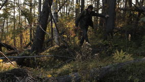 A middle aged man with a beard wearing grey pants, green jacket and yellow boots with a backpack getting rough windfall stock footage