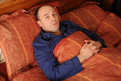 Middle aged man in bed Royalty Free Stock Photos