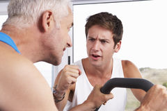 Middle Aged Man Being Encouraged By Personal Trainer In Gym Stock Images