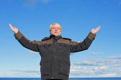 Middle-aged man on blue sky of the background. Royalty Free Stock Photos