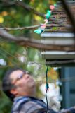 Middle aged man with blurred face hangs christmas lights. Man hanging Christmas lights during winter from a ladder royalty free stock images