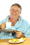 Middle Aged Man At Breakfast. Nerdy middle aged man smiling while having breakfast and reading the paper Stock Photography