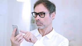 Middle aged man browsing internet on smartphone stock footage