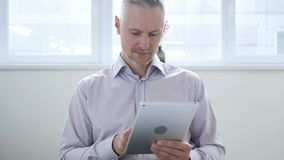 Middle aged man browsing internet on tablet in office. 4k , high quality stock video
