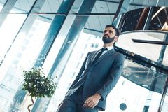 Businessman in a fromal suit in a business center enter the building bottom view. Middle-aged man businessman in a business center enter the glass doors Royalty Free Stock Image