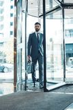 Businessman in a fromal suit in a business center enter the building with briefcase. Middle-aged man businessman in a business center enter the glass doors Royalty Free Stock Photos