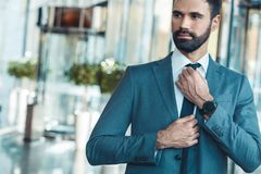 Businessman in a fromal suit in a business center tighten a tie. Middle-aged man businessman in a business center tighten a tie thoughtful Royalty Free Stock Images