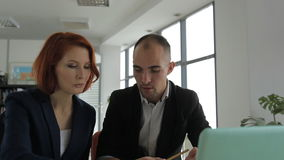 A middle-aged man businessman business manager. Not a young man businessman business manager talking with his client a beautiful attractive woman sitting at the stock footage