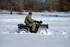 Middle-aged man in camo riding four wheeler. Man in camo riding quad wheeler through the snow Stock Photos