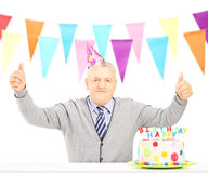Middle aged man celebrating his birthday giving thumbs up Stock Photos
