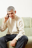 Middle-aged man on cellphone. Middle-aged man sitting on green on sofa talking on cellphone Royalty Free Stock Photos
