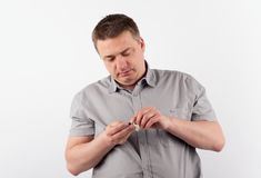Middle aged man changing his hearing aid's battery Stock Image