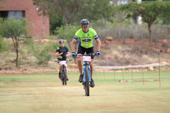 Middle aged man chasing to the finish line at Mountain Bike Race Royalty Free Stock Images