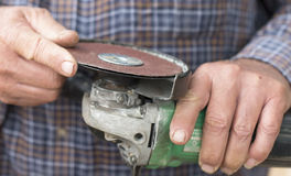 Middle-aged Man Checking Angle Grinder. Stock Image