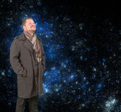 Middle-aged man in a coat looking up on starry universe background Royalty Free Stock Photos