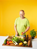 Middle-aged man cook fresh salad Royalty Free Stock Photos