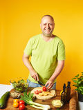 Middle-aged man cook fresh salad Royalty Free Stock Images