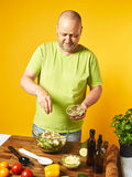 Middle-aged man cook fresh salad Stock Photos