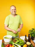 Middle-aged man cook fresh salad Royalty Free Stock Image