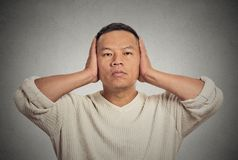 Middle aged man covering his ears observing Royalty Free Stock Photos