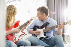 Middle-aged man with daughter playing guitars at home Stock Photo