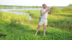 A middle aged man does yoga and breathing exercises on the lake in the morning. Overall plan stock video footage