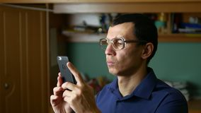 Middle-aged man doing selfie photo with glasses and shirt indoor Royalty Free Stock Photo