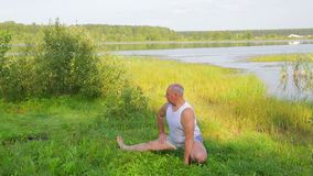 A middle-aged man doing stretching exercises on the lake in the morning. Overall plan stock footage