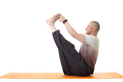 Middle aged man doing yoga in studio. Side view. Stock Photos