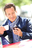 Middle-aged man drinking coffee and websurfing Stock Images