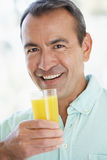 Middle Aged Man Drinking Fresh Orange Juice stock photo