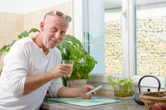 Middle-aged man drinking a glass of juice stock image