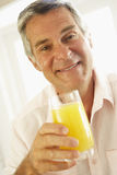 Middle Aged Man Drinking A Glass Of Orange Juice Royalty Free Stock Photos