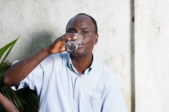 Middle-aged man drinking water in a glass. Middle-aged man sitting near a wall and drinking mineral water royalty free stock photos